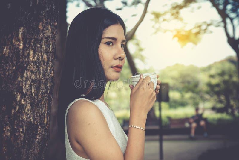 Jonge de koffiemok van de vrouwenholding in openbaar park stock afbeelding