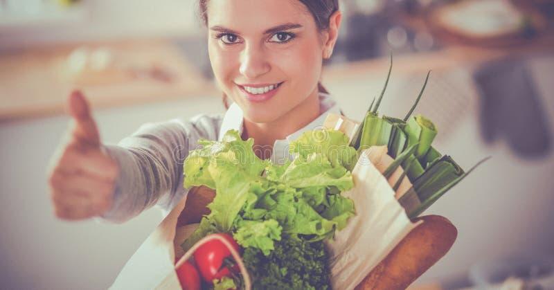 Jonge de kruidenierswinkel van de vrouwenholding het winkelen zak met groenten en het tonen van o.k. stock fotografie