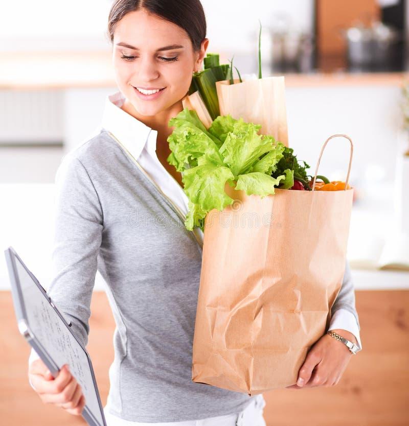 Download Jonge De Kruidenierswinkel Van De Vrouwenholding Het Winkelen Zak Met Groenten Status In De Keuken Stock Foto - Afbeelding bestaande uit gelukkig, peper: 107705736