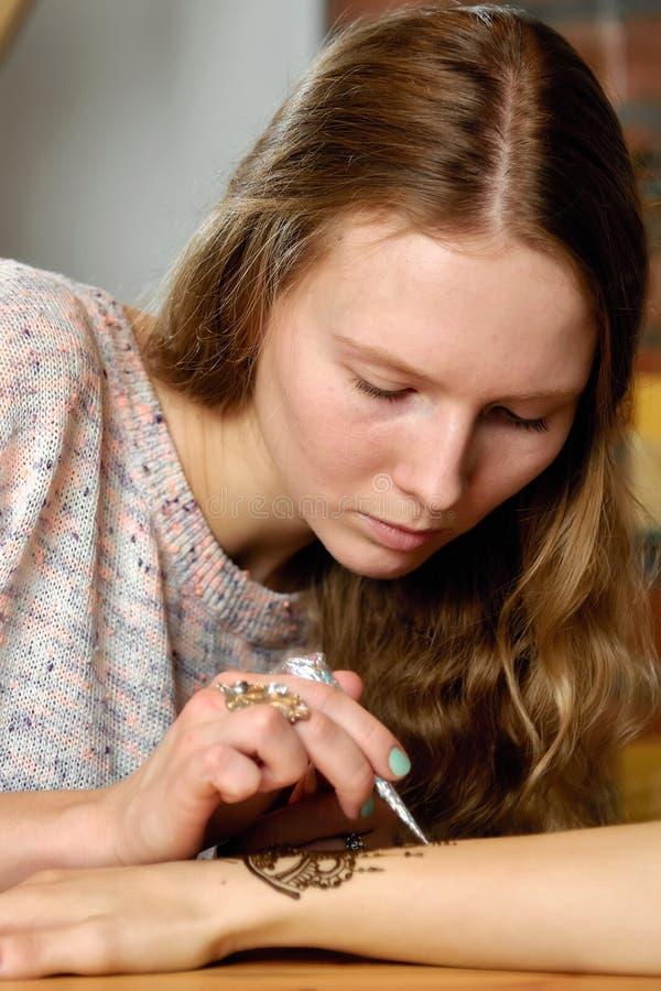Jonge de kunstenaar van vrouwenmehendi het schilderen henna op de hand royalty-vrije stock afbeelding