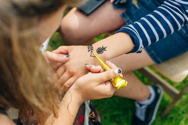 Jonge de kunstenaar van vrouwenmehendi het schilderen henna op de hand stock fotografie
