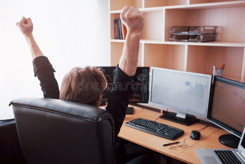 Jonge de makelaar van de voorraadhandelaar het uitrekken zich handen op het werk, bereikte hij eerst groot succes op de effectenb stock foto's