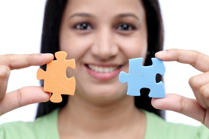 Jonge de puzzelstukken van de vrouwenholding stock fotografie