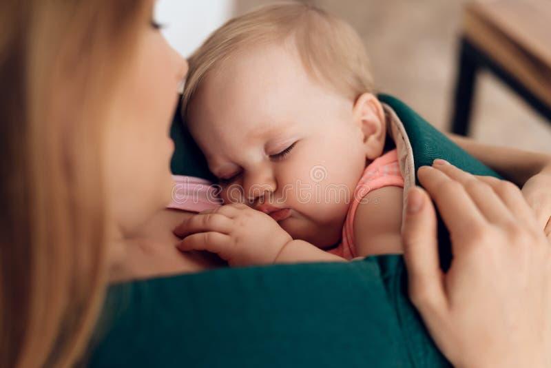 Jonge de slaapbaby van de moederholding in babyslinger stock foto's