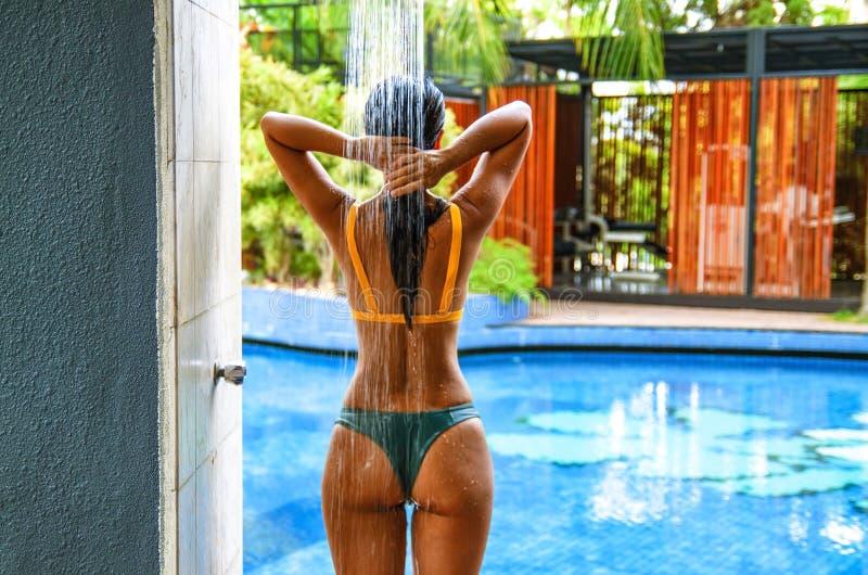 Jonge de slijtagebikini die van het sportenmeisje zich onder de openluchtpooldouche bevinden Speelse tijd als waterval stock afbeelding