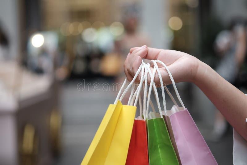 Jonge de verkoop van de vrouwenholding het winkelen zakken het concept van de consumentismelevensstijl in het winkelcomplex stock foto