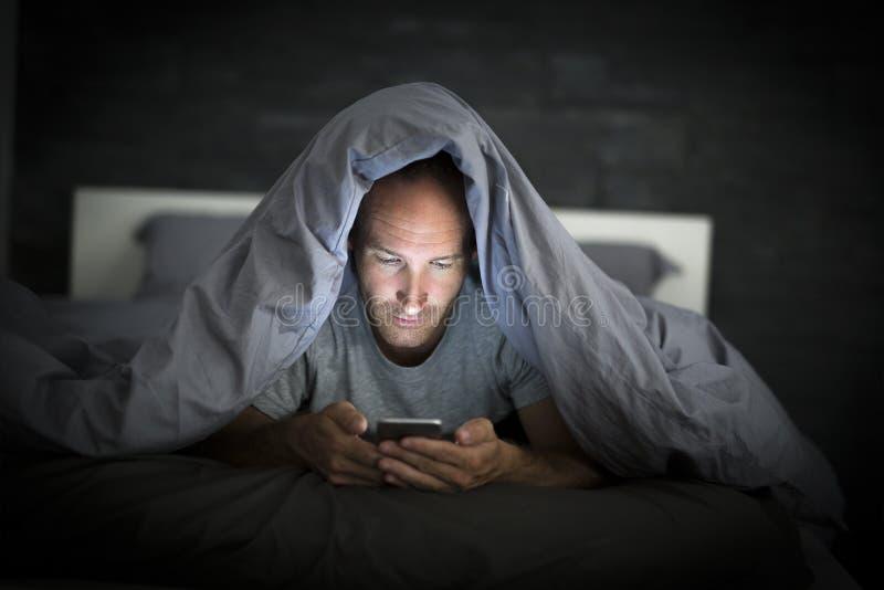 Jonge de verslaafdenmens van de celtelefoon wakker laat bij nacht in bed die smartphone gebruiken royalty-vrije stock afbeelding