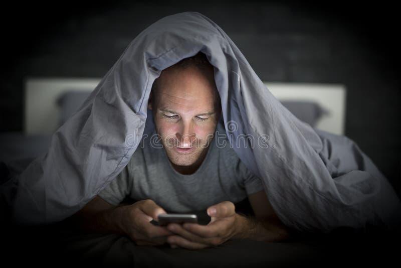Jonge de verslaafdenmens van de celtelefoon wakker laat bij nacht in bed die smartphone gebruiken stock fotografie