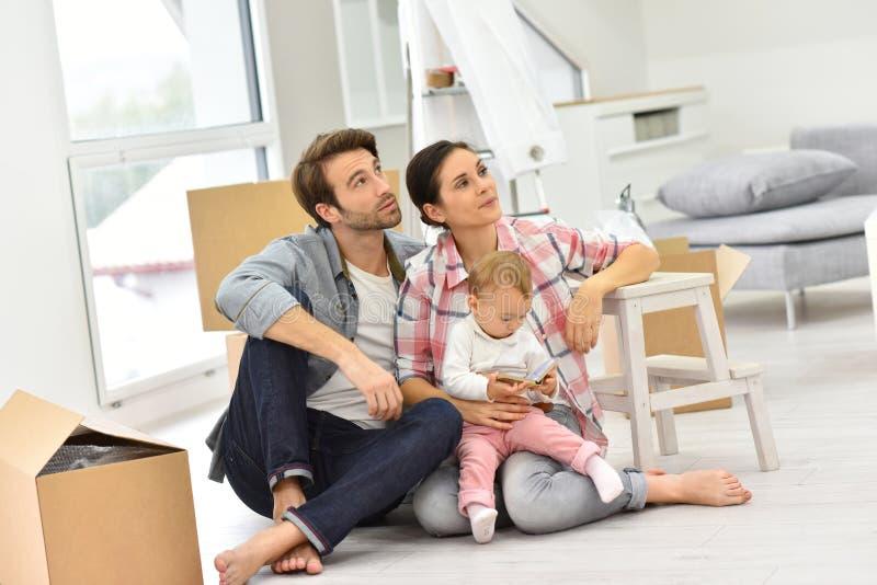 Jonge die familie onlangs in nieuw huis wordt bewogen stock afbeelding