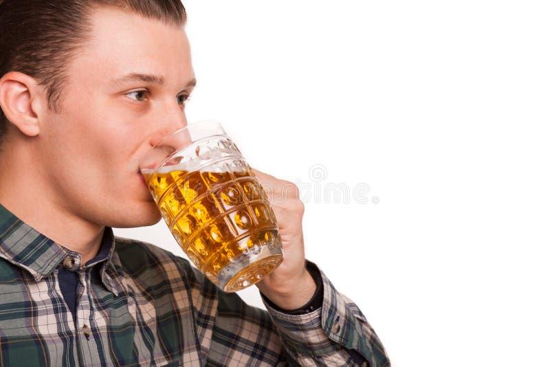 Jonge die mens het drinken bier op wit wordt geïsoleerd royalty-vrije stock afbeeldingen