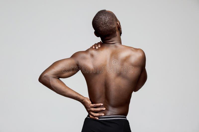 Jonge die mens met rugpijn op wit wordt geïsoleerd stock afbeelding