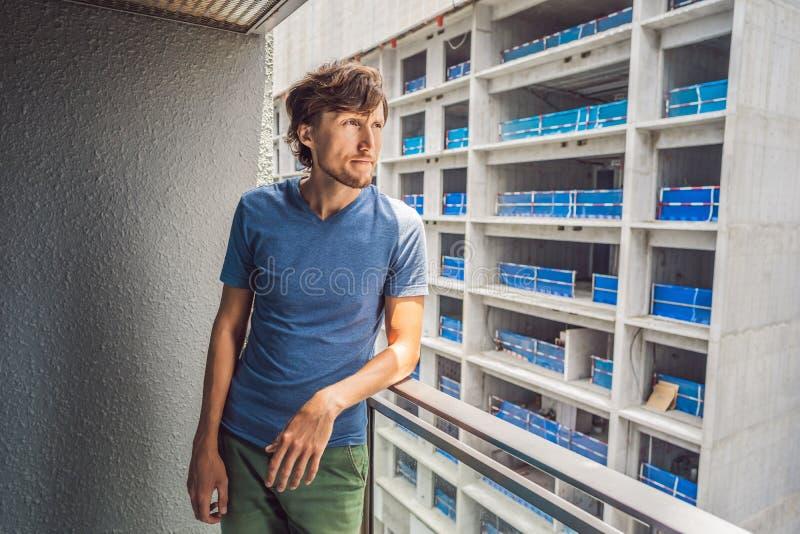 Jonge die mens op het balkon door de de bouwwerken buiten wordt geërgerd Lawaaiconcept Luchtvervuiling door de bouw van stof royalty-vrije stock afbeeldingen