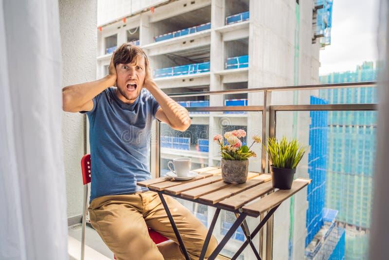 Jonge die mens op het balkon door de de bouwwerken buiten wordt geërgerd Lawaaiconcept Luchtvervuiling door de bouw van stof stock foto