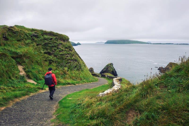 Jonge die mensengangen langs weg door Iers landschap wordt omringd royalty-vrije stock afbeeldingen