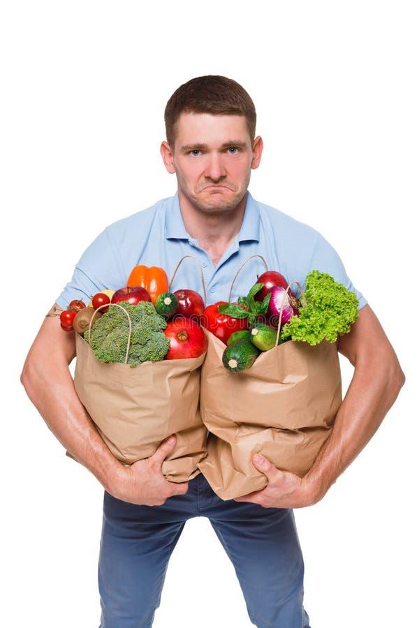 Jonge die mensenholding het winkelen zakkenhoogtepunt van groenten op witte achtergrond wordt geïsoleerd royalty-vrije stock afbeeldingen