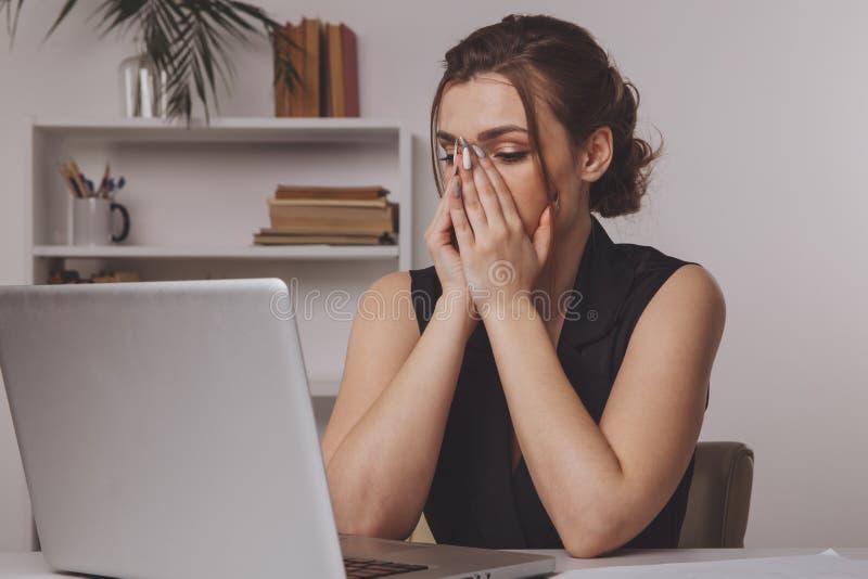 Jonge die onderneemster van het werk in bureau wordt vermoeid stock foto's