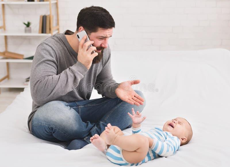 Jonge die vader bij schreeuwende baby thuis wordt gefrustreerd royalty-vrije stock fotografie