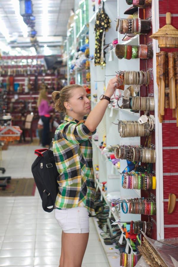 Jonge die vrouw met de keus van ornamentals wordt teleurgesteld Het winkelen en giftenconcept royalty-vrije stock foto