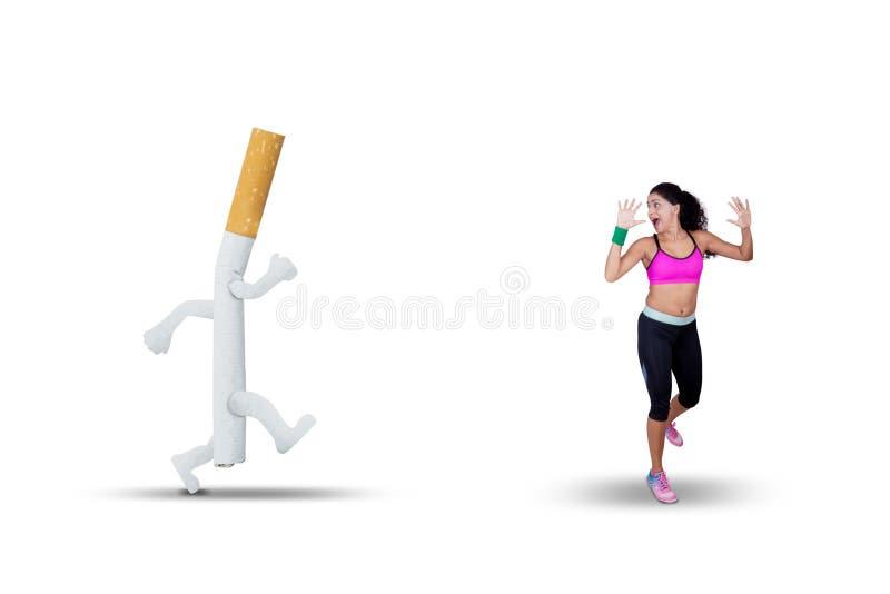 Jonge die vrouw met een sigaret op studio wordt achtervolgd stock fotografie