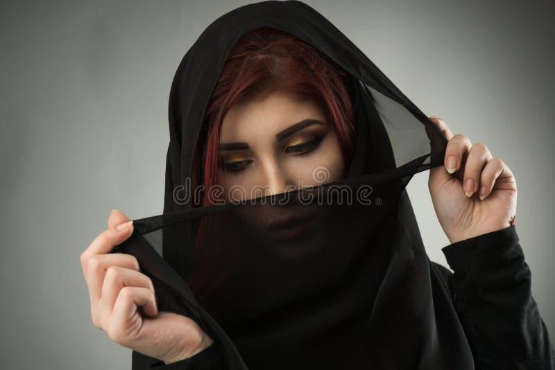 Jonge die vrouw met hoofd door een zwarte sluier wordt behandeld stock foto