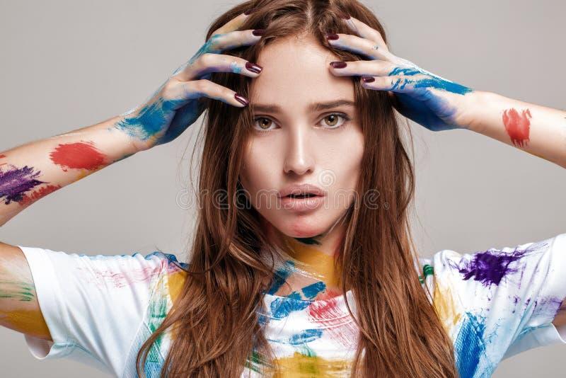 Jonge die vrouw in multicolored verf wordt gesmeerd stock foto's
