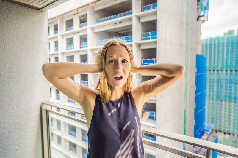 Jonge die vrouw op het balkon door de de bouwwerken buiten wordt geërgerd Lawaaiconcept Luchtvervuiling door de bouw van stof royalty-vrije stock foto
