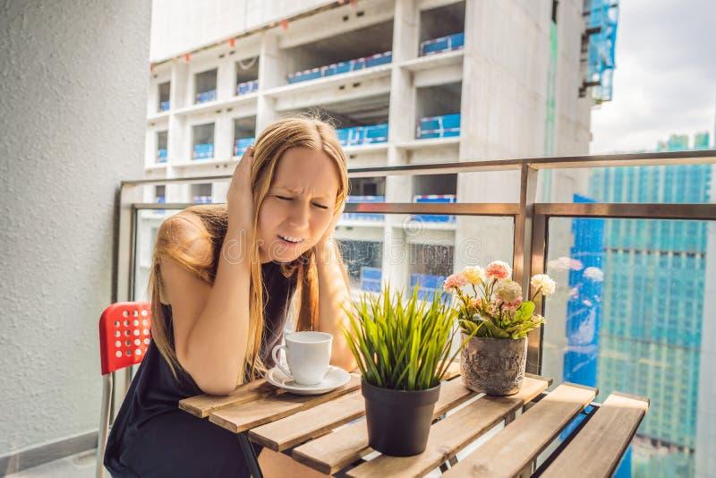 Jonge die vrouw op het balkon door de de bouwwerken buiten wordt geërgerd Lawaaiconcept Luchtvervuiling door de bouw van stof stock afbeeldingen