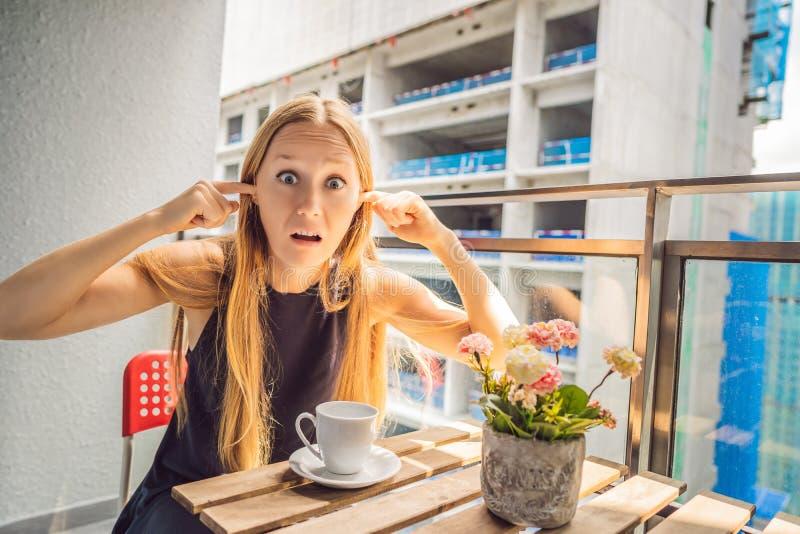 Jonge die vrouw op het balkon door de de bouwwerken buiten wordt geërgerd Lawaaiconcept Luchtvervuiling door de bouw van stof royalty-vrije stock afbeelding