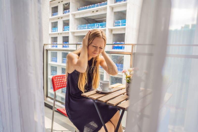 Jonge die vrouw op het balkon door de de bouwwerken buiten wordt geërgerd Lawaaiconcept Luchtvervuiling door de bouw van stof stock afbeelding