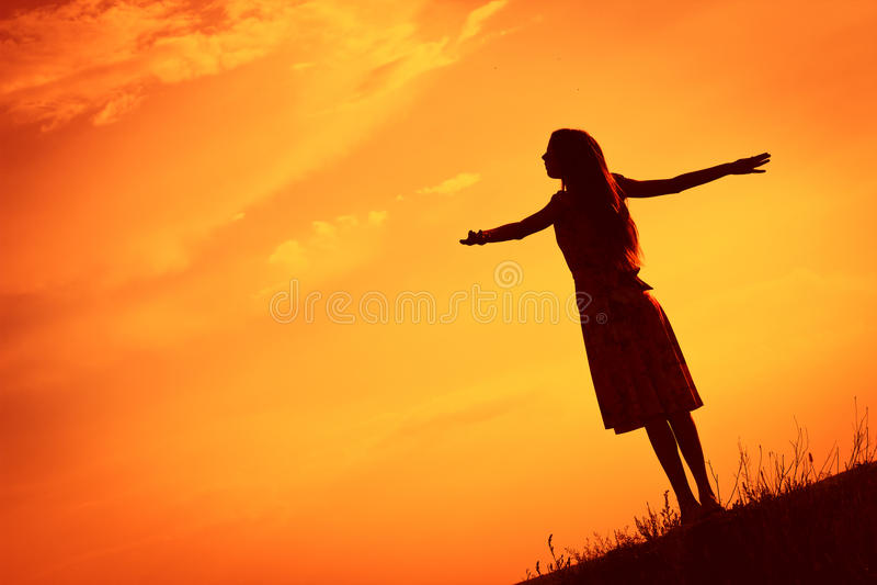 Jonge die vrouw tegen gloeiende oranje hemel wordt gesilhouetteerd stock afbeeldingen