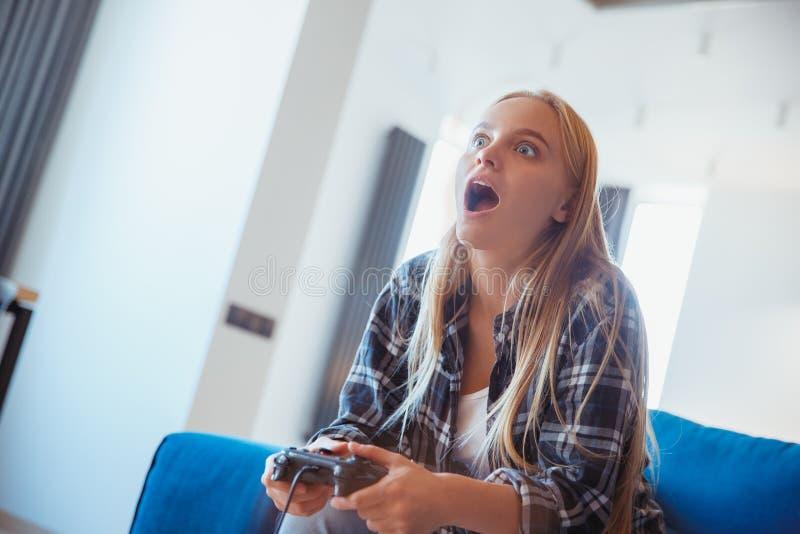Jonge die vrouw thuis in de woonkamer door het spel wordt geschokt royalty-vrije stock afbeeldingen