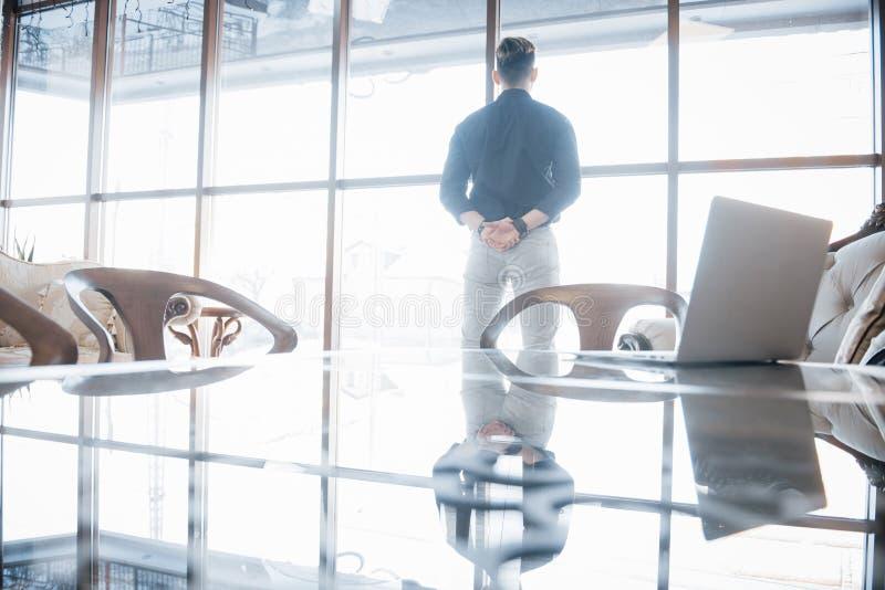 Jonge directeur en leider die zich vol vertrouwen, in het hoogste vloerbureau bevinden, die de stad hieronder door bekijken stock foto's