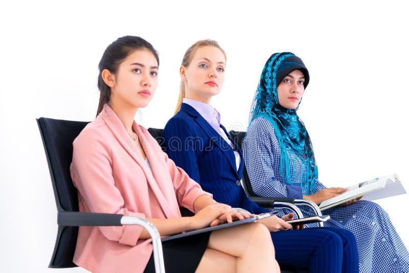 Jonge diverse bedrijfsvrouwenzitting op een rij voor baan binnen stock fotografie