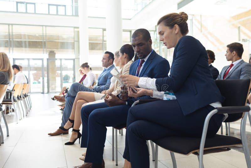 Jonge diverse die stafmedewerkers in conferentieruimte worden gezeten, het spreken stock fotografie