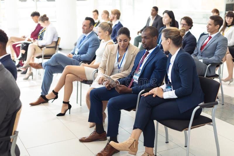 Jonge diverse stafmedewerkers die in conferentieruimte worden gezeten, het spreken stock afbeelding