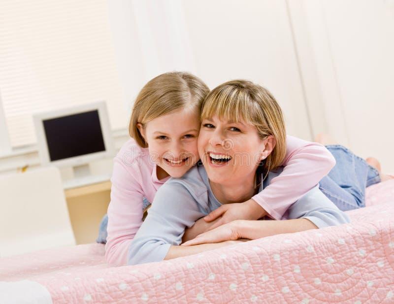 Jonge dochter die moeder koestert terwijl het liggen op bed stock fotografie