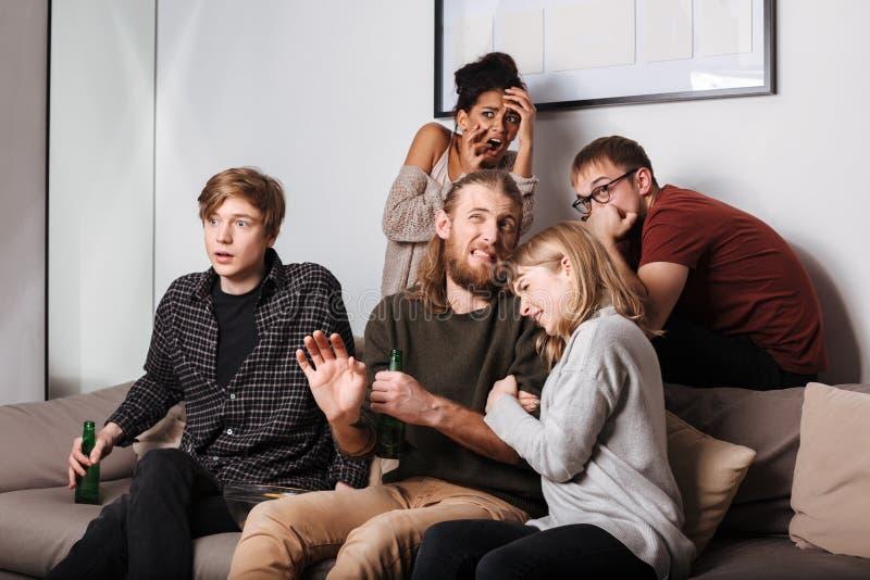 Jonge doen schrikken vrienden die frightenedly verschrikkings op film samen met bier in woonkamer letten stock fotografie