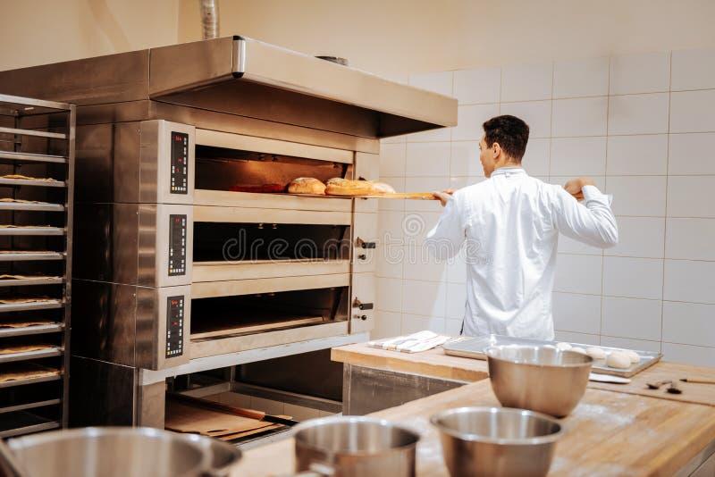 Jonge donker-haired bakker die de broden van brood nemen uit de oven stock afbeelding