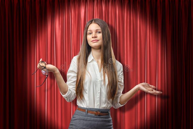 Jonge donkerbruine bedrijfsvrouw die twijfel met palmen omhoog op de rode achtergrond van stadiumgordijnen tonen stock afbeelding