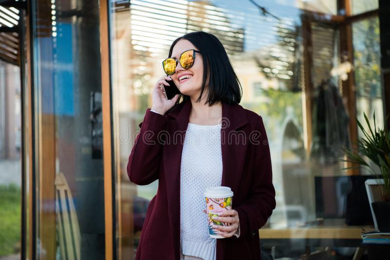 Jonge donkerbruine het drinken koffie die rond de stad lopen Het dragen van laag, heldere rode lippen, die tegen het venster van  stock afbeeldingen