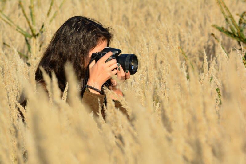 Jonge donkerbruine meisjesfotograaf in actie royalty-vrije stock fotografie