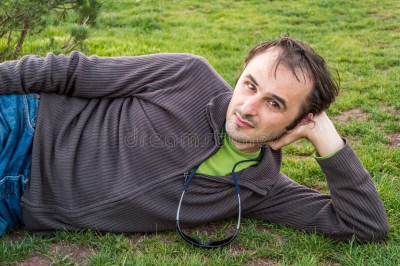 Jonge donkerbruine mens in het toevallige kleding ontspannen op gras in park stock foto