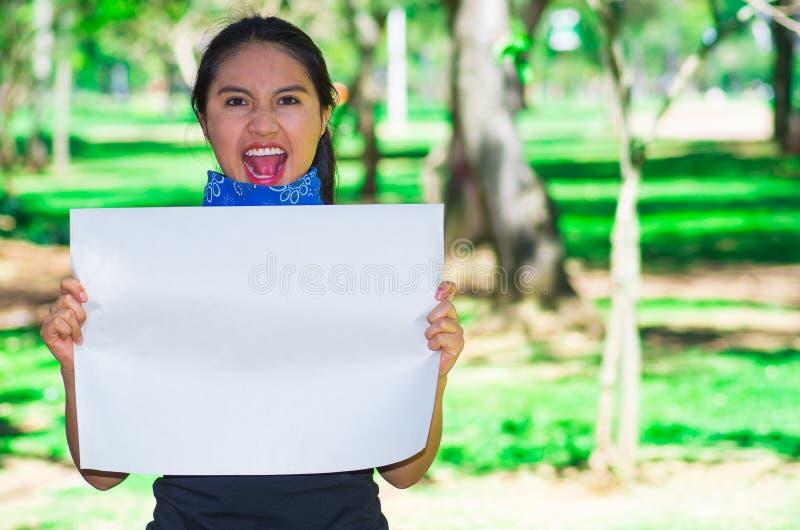 Jonge donkerbruine vrouw die blauwe bandana dragen rond hals, die witte affiche houden die in openlucht het onder ogen zien van c royalty-vrije stock foto's