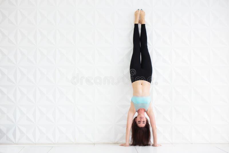 Jonge donkerbruine vrouw die een handstand over een witte muur doen stock afbeeldingen