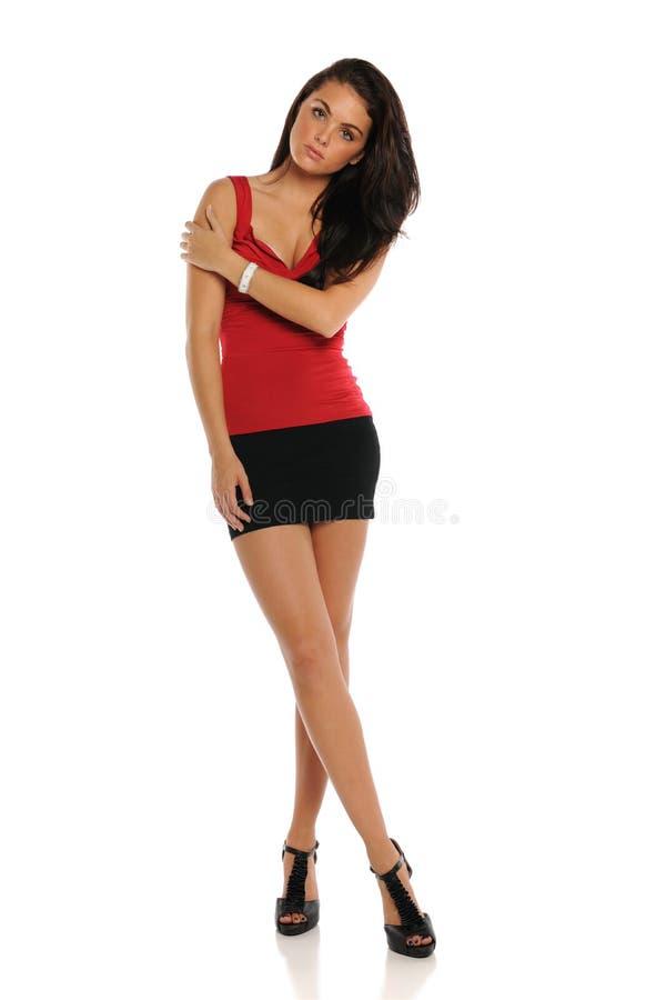 Jonge donkerbruine vrouw die een korte rok draagt stock afbeelding