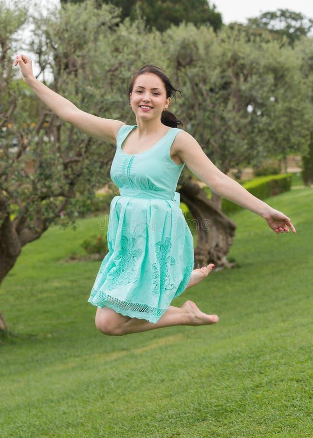 Jonge donkerbruine vrouw die in kleding bij in openlucht springen stock afbeelding