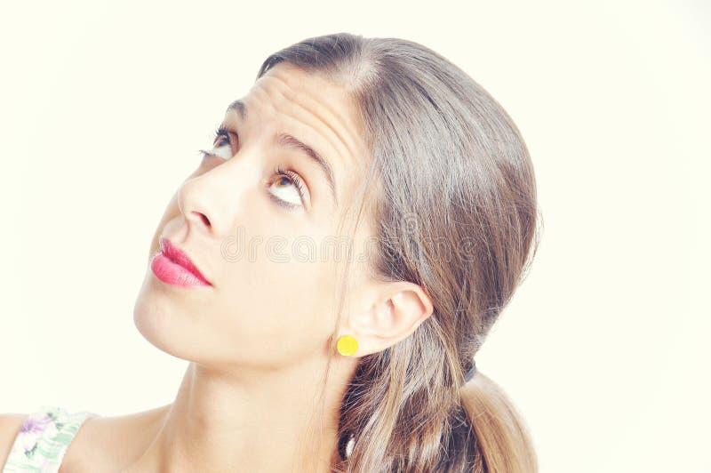 Jonge donkerbruine vrouw die omhoog kijken stock afbeelding