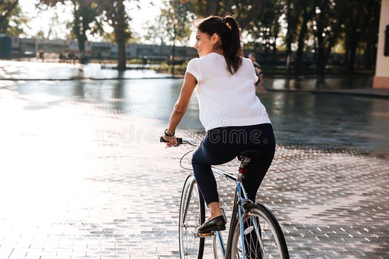 Jonge donkerbruine vrouw die op fiets in stadsstraat berijden royalty-vrije stock fotografie