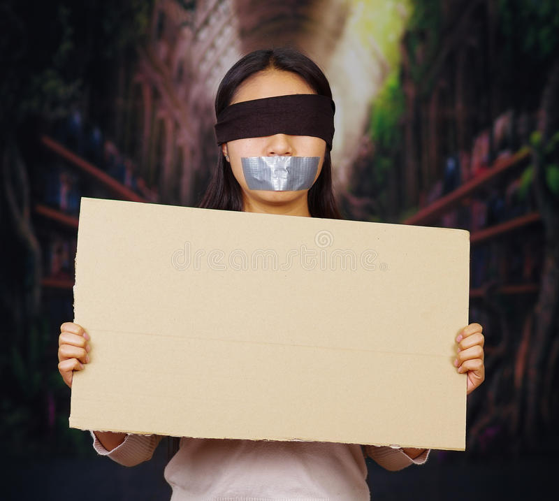 Jonge donkerbruine vrouw die witte sweater, geblinddochte zwarte kabel dragen en gekneveld met buisband, die leeg teken steunen royalty-vrije stock foto's