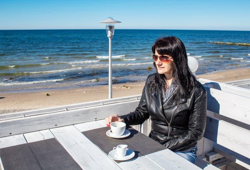 Jonge donkerbruine vrouw het drinken koffie in een openluchtkoffie dichtbij het overzees royalty-vrije stock foto's